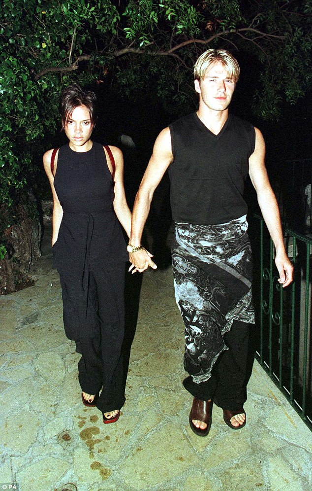 David Beckham rocking a skirt and Victoria wearing the pant-suit.