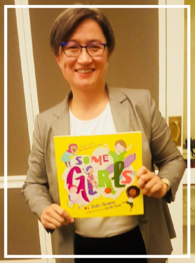 Senator Penny Wong holding a copy of SOME GIRLS for her daughters