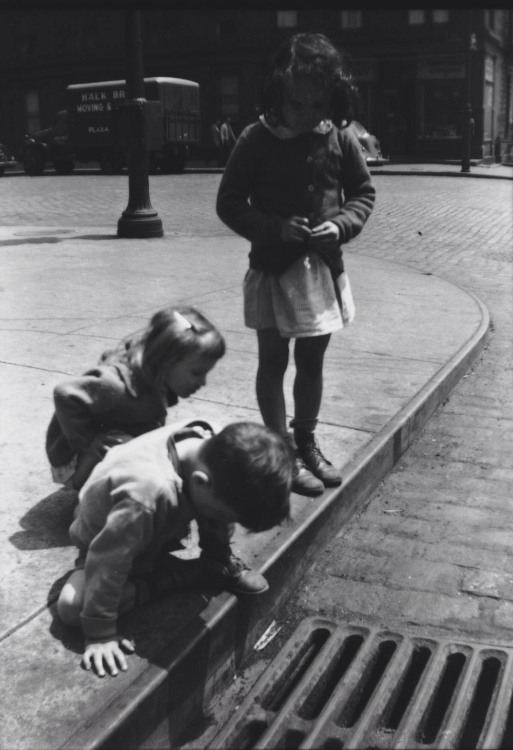 Children in New York City, circa 1930, peering down a sewer grate. Photo by Walker Evans.