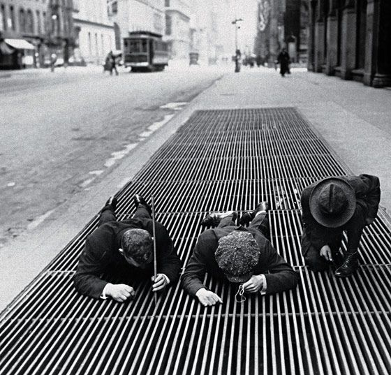 Scouring for change through a street grate during the Depression, New York, 1930.