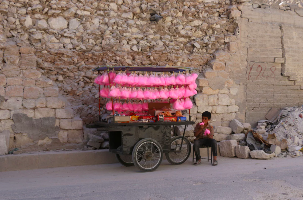 A CHILD SELLS CANDY FLOSS ON A STREET CART IN AL-BAB CITY IN THE NORTH OF ALEPPO PROVINCE, 2017. PHOTOGRAPH: ZEIN AL RIFAI/AFP/GETTY IMAGES