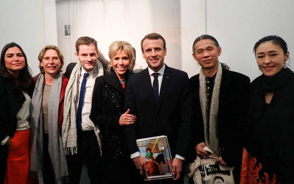 French President Emmanuel Macron and his wife Brigitte, surrounded by   Sam Stourdzé (Director of Rencontres d'Arles and co-founder of Jimei x Arles), RongRong (photographer, founder of Three Shadows and co-founder of Jimei x Arles) & inri (photographer and founder of Three Shadows), and Doors agency founders Bérénice Angremy (director of Jimei x Arles) and Victoria Jonathan (general manager of Jimei x Arles) at   Ullens Center for Contemporary Art (UCCA) on 9 January 2018