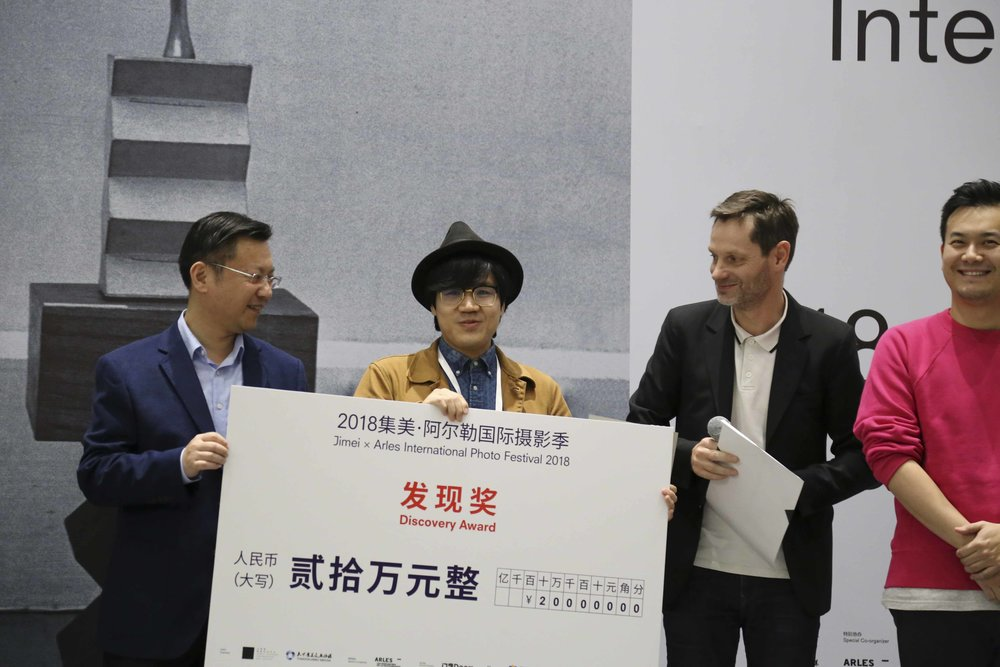Lei Lei receiving the Jimei x Arles Discovery Award from Lai Zhaohui (Jimei district), jury members Sam Stourdzé (director of Rencontres d'Arles) and David Chau (collector and art entrepreneur)