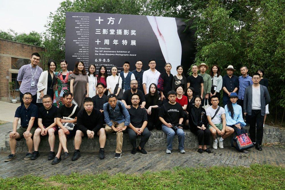 Photo de groupe des artistes et commissaires de l'exposition  Ten Directions: The 10th Anniversary Exhibition of the Three Shadows Photography Award