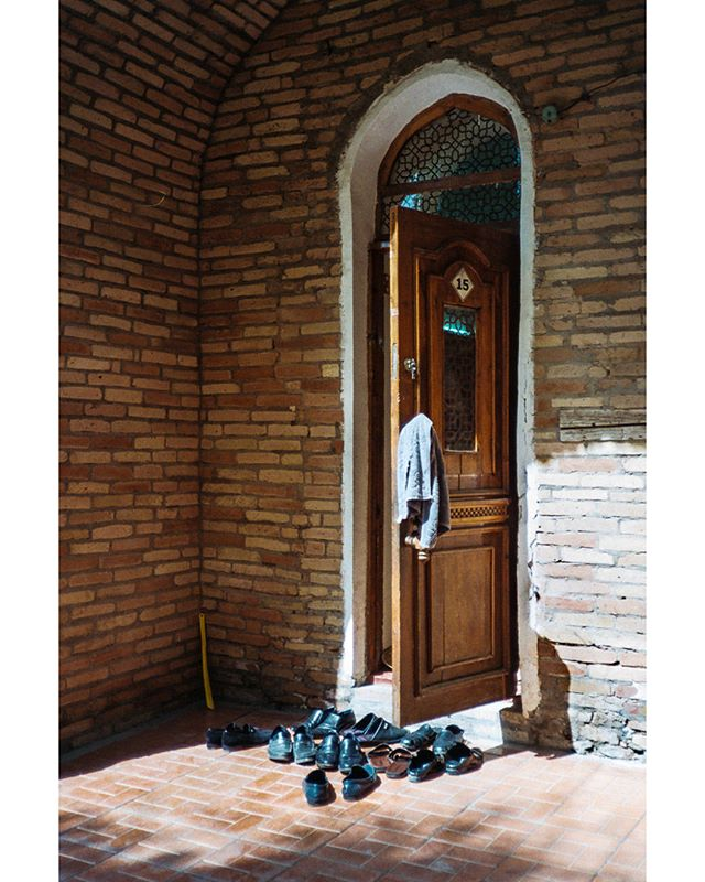 Prayer time at Kukeldash Madrasah. Aug 30, 2018. Tashkent, Uzbekistan. . . . . . . . . . #madrasah #Uzbekistan #travelphotography #religion #filmisnotdead #tashkent #travel #adventure #shoes #prayer #door #architecture #human #art #film #35mm #olympusxa #filmphotography #vista #asia #sun #shadow #street #streetphotography #brick #madrasah