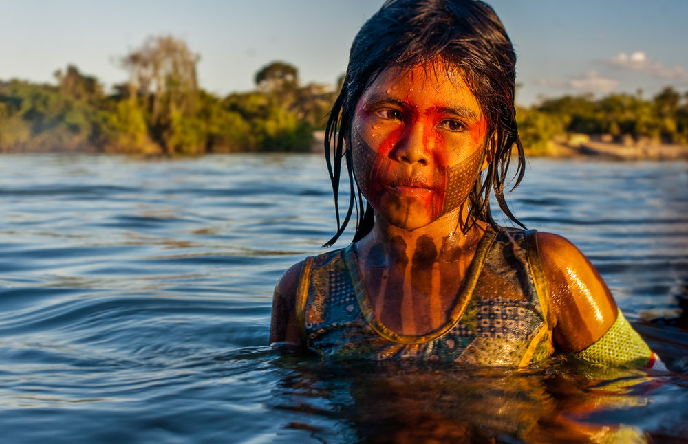 The Xingú river is intimately woven into the fabric of Kayapó life. This young girl's eyes speak of a beloved waterway about to be dammed forever, of pride in her people's traditions, of fear for a future unknown, and of the innocence that every child deserves to live with.