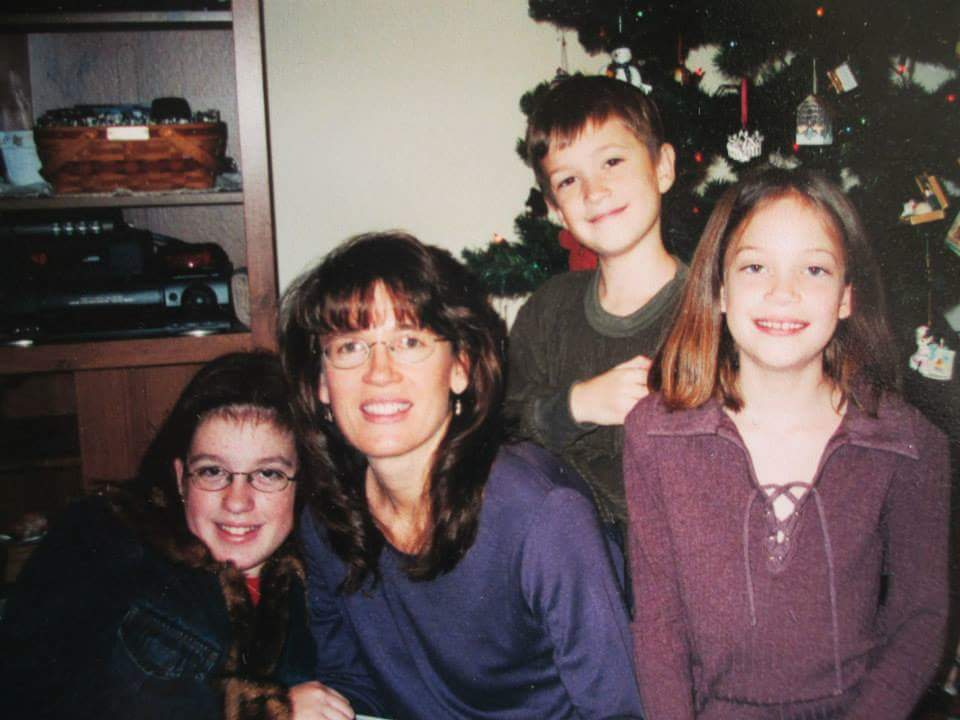 My brither, sister and I with our mom in front of the tree.