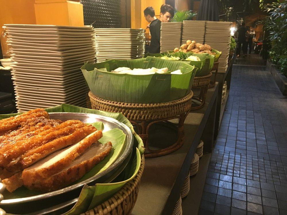 Crispy pork, rice noodles in banana leaf bowls