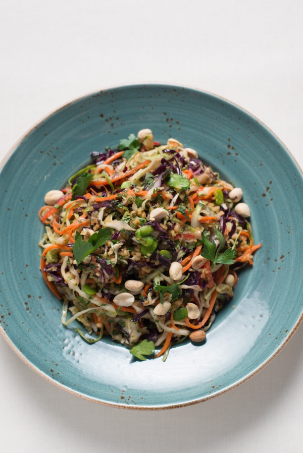 Photo by Kristen Loken    Asian Slaw with Ginger-Peanut Dressing   Ingredients  For the Dressing  · 1/4 cup honey  · 1/4 cup green peanut oil  · 1/4 cup unseasoned rice vinegar  · 1 tablespoon soy sauce  · 1 teaspoon roasted peanuts pureed in green peanut oil  · 1 tablespoon peanut butter  · 1/2 teaspoon salt  · 1/2 teaspoon Sriracha sauce  · 1 tablespoon minced fresh ginger  · 1 large garlic clove, minced  For the Slaw  · 4 cups prepared shredded coleslaw  · 2 cups prepared shredded carrots  · 1 red bell pepper, thinly sliced into bite-sized pieces  · 1 cup cooked and shelled fava beans  · 2 medium scallions, finely sliced  · 1/2 cup chopped salted peanuts  · 1/2 cup loosely packed chopped fresh cilantro  Instructions  1. Make the dressing by combining all of the ingredients in a medium bowl. Stir until the peanut butter is dissolved. Set aside.  2. Combine all of the slaw ingredients in a large bowl. Add the dressing and toss well. Let sit at least ten minutes so vegetables have a chance to soak up the dressing. Taste and adjust seasoning if necessary. Serve cold.  Courtesy of The Culinary Institute of America - St. Helena, California