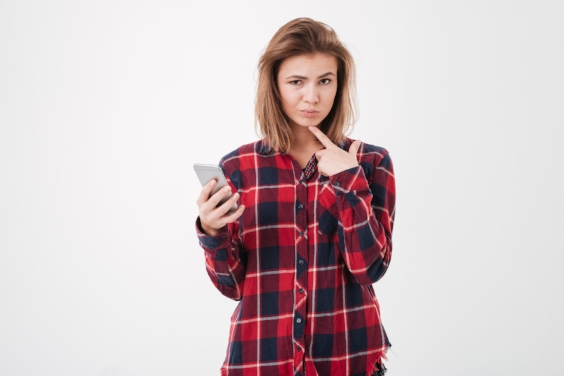 graphicstock-pensive-young-cute-girl-in-plaid-shirt-holding-smartphone-and-looking-at-camera-over-white-background_rOXF_h3Ihl.jpg