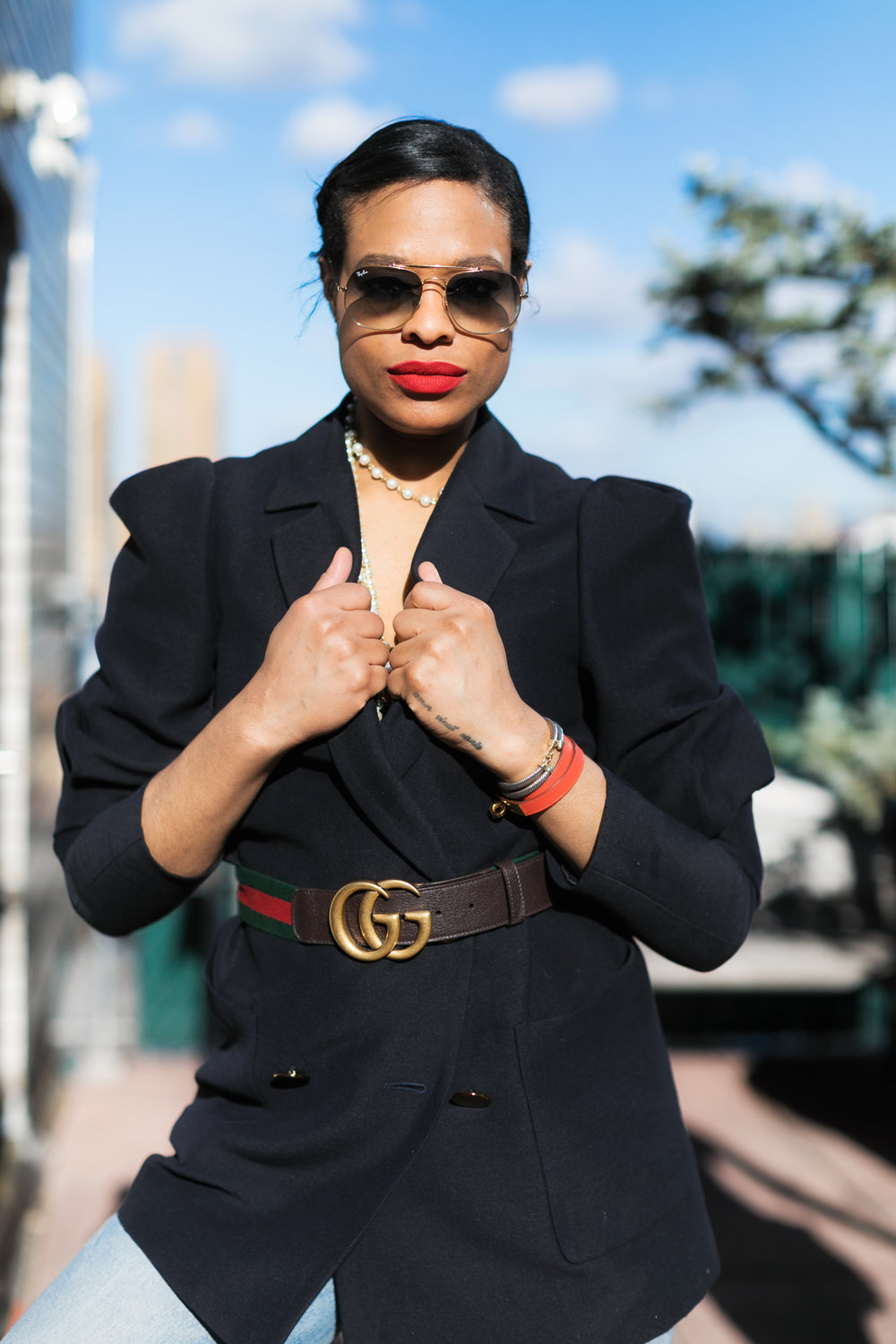 Blazer: Zara. Pearl necklaces: Chanel. Bra: Victoria's Secret. Belt: Gucci. Jeans: Re/Done. Shoes. Prada. Sunglasses: Ray-Ban.