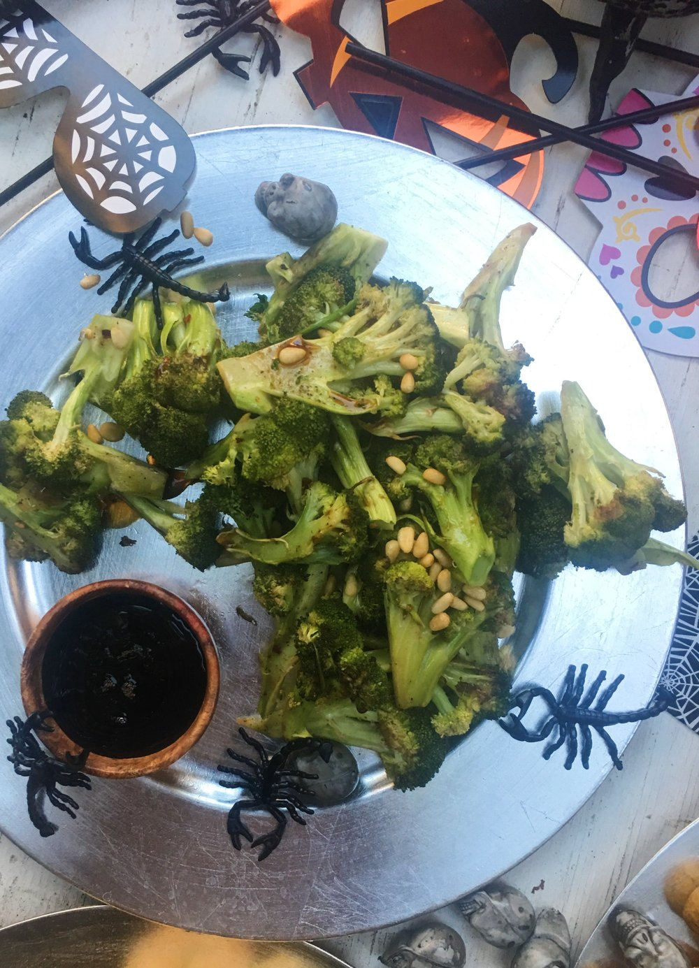 Broccoli and pine nuts all roasted together are delicious -- and nutritious for kids. It's Halloween, so the pomegranate molasses dipping sauce is both seasonal and also a way for kids to pretend this is candy. You know better.