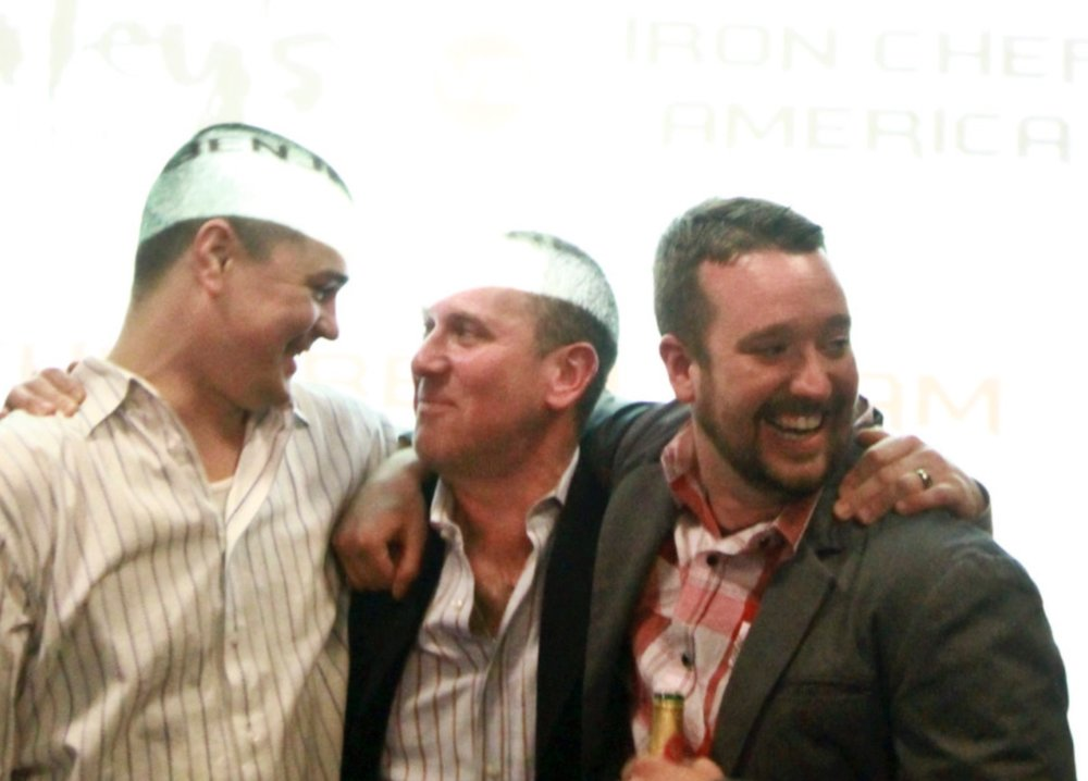 Patrick McKee (left) with his mentor and team lead, Vitaly Paley (center), after their Iron Chef America win over treasured US chef Jose Garces.