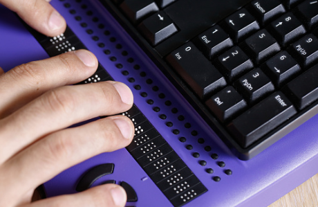 Person typing on a braille keyboard