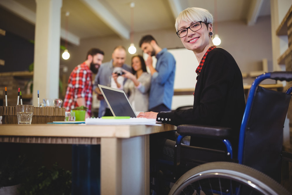 Smiling woman in a wheelchair doing design work on her Microsoft laptop with her colleagues behind her