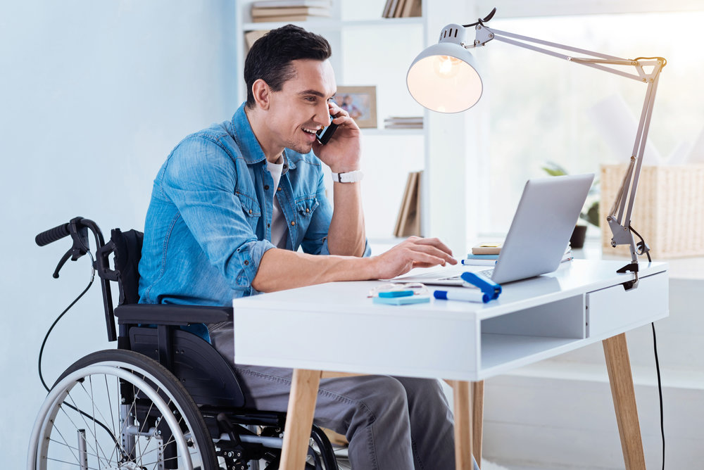 Smiling man in a wheelchair working on his Microsoft laptop in a sunny home-office while having a conversation with someone on his cellphone
