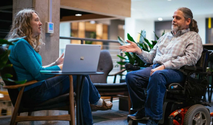 Woman working on a Microsoft laptop collaborating via discussion with a man in an electric wheelchair. Photo retrieved from web-page:  https://www.microsoft.com/en-us/diversity/inside-microsoft/cross-disability/hiring.aspx ; image:  https://img-prod-cms-rt-microsoft-com