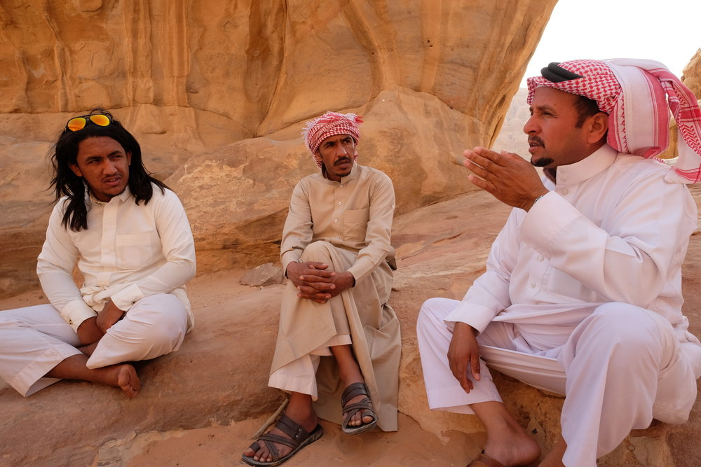Bedouin guides sit together chatting in the shade while tourists explore Wadi Rum.