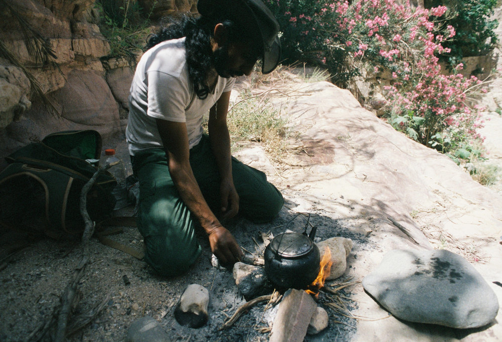 A Bedouin guide prepares tea during a rest stop while hiking in the Dana Reserve, Jordan. The sugary drink made from local herbs helps to replenish electrolytes lost in the extreme heat.