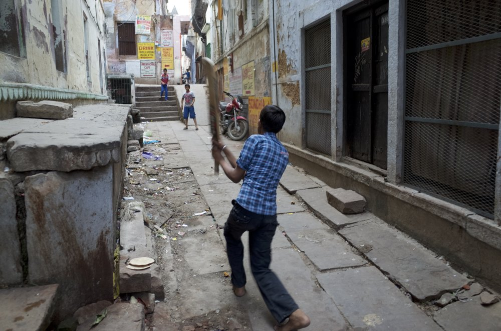 Boys play cricket along the narrow alley ways of Varanasi, India.                         Photo By: Sarah Tesla