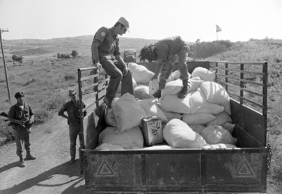 A Syrian food and water supply convoy being inspected by members of the Austrian Battalion with UNDOF near the village of Beit Jinn, before it can proceed on its way through an Israeli held area to the village of Hadar. 21 June 1974 Syria  UN Photo/Yutaka Nagata