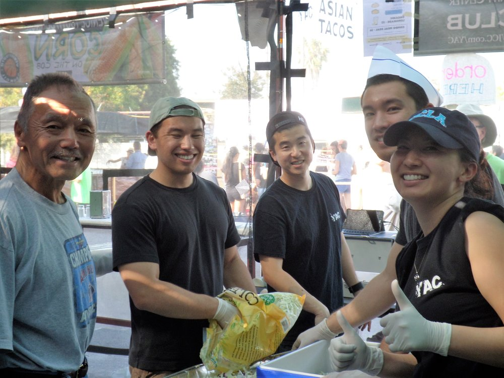 Boardmembers Keith Kawamoto and Steven Sharp volunteer for a shift at YAC's Taco Booth.