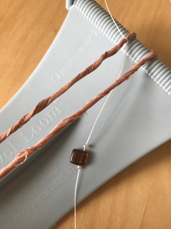 5. Take a nice deep breath and welcome yourself to the beading process! Thread you beading needle and guide it under the two strands of ribbon, coming out on the right side.String on one seed bead, one two-hold bead and a second seed beed.