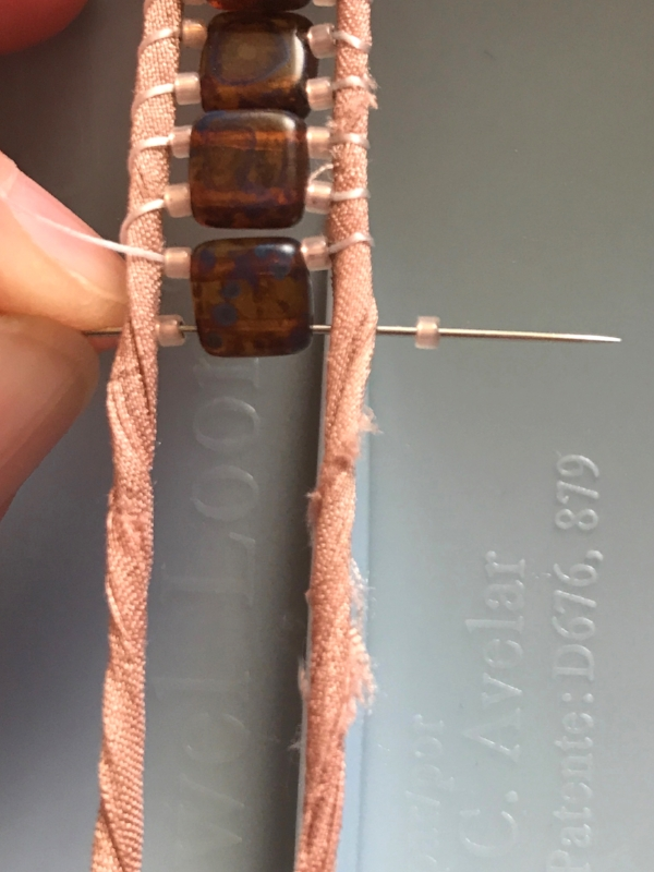 9. Thread on the second seed bead.