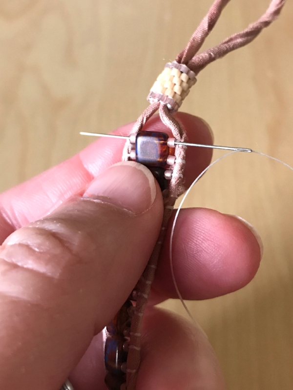 14. Cut a new length of beading thread and thread your needle. Insert it through the three beads on one end of your bracelet. I started with the loop end, but it doesn't really matter.