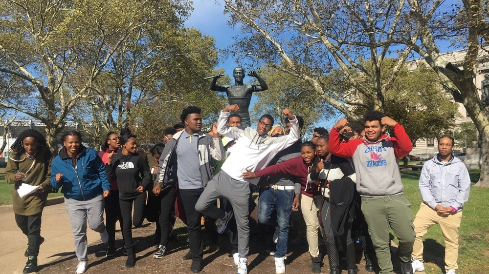 Students standing in front of the Jesse Owens statue