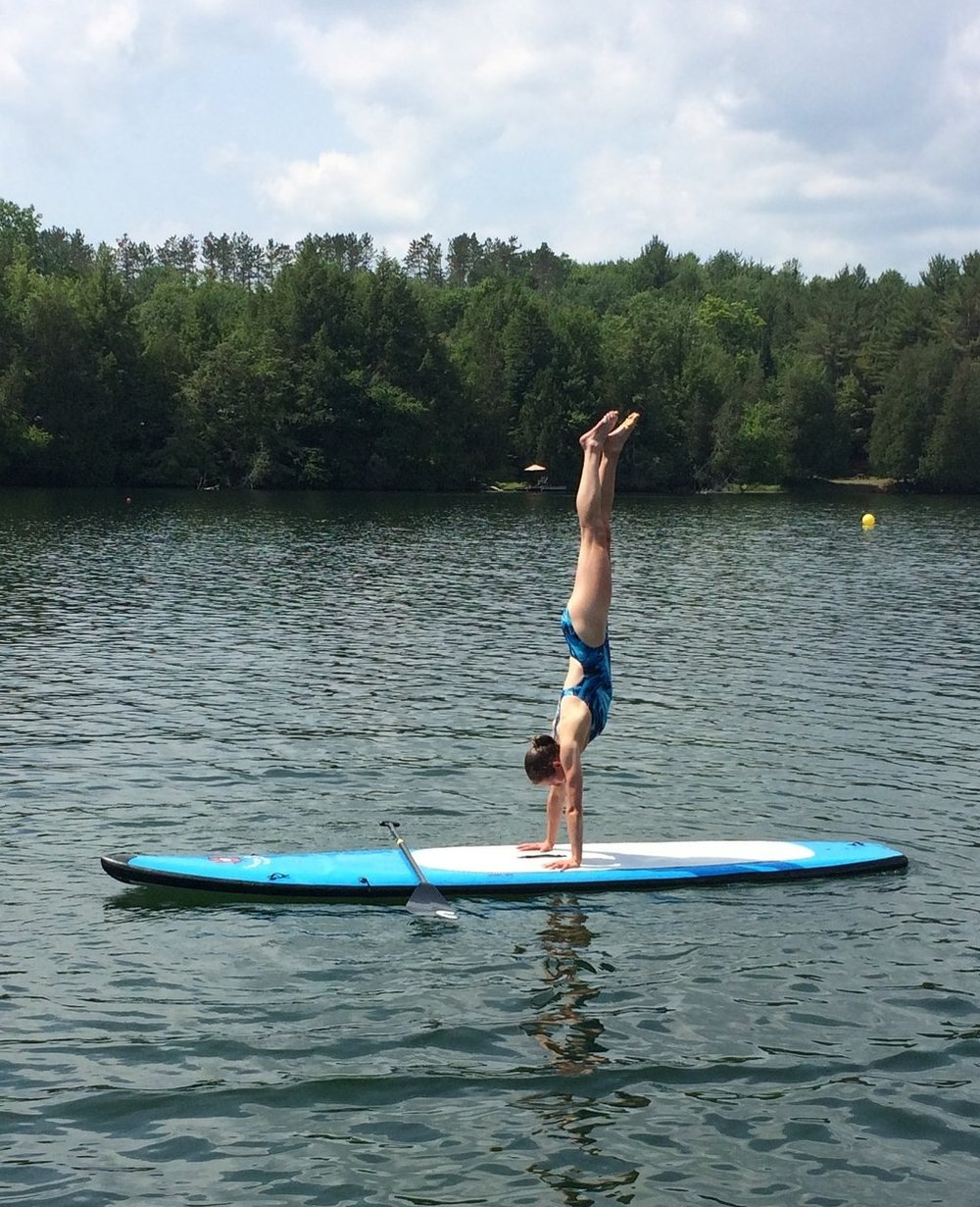 Paddle board handstands on the lake