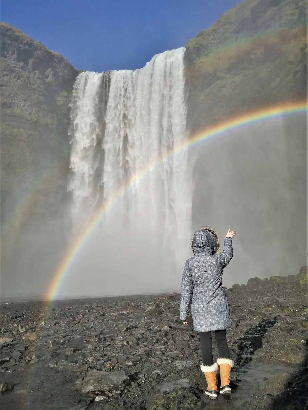Skogafoss waterfall with a rainbow is one of the prettiest sites in Iceland. This Iceland waterfall is really easy to get to off the main road, and you can climb steps to the top. #iceland #waterfall #icelandtravel #icelandwaterfalls #skogafoss #skogafossiceland #skogafosswaterfalliceland #waterfalls #waterfallsaroundtheworld #traveldestinations #traveltips