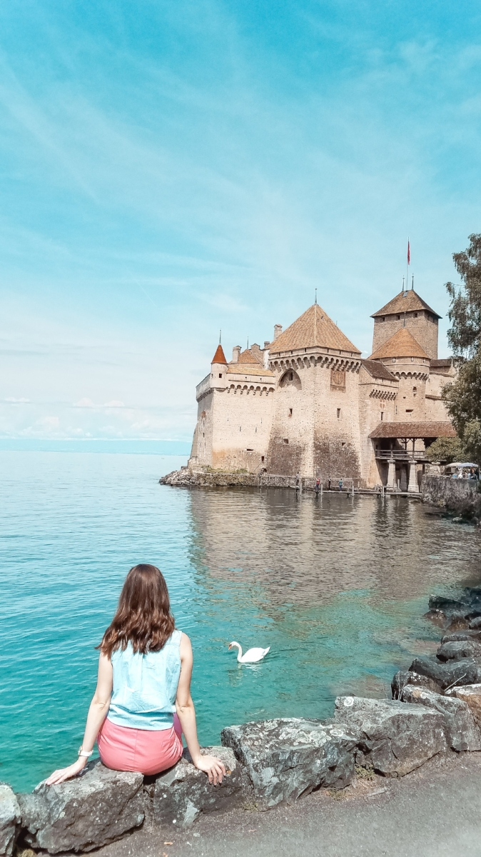 The Swiss castle of Chateau de Chillon is on Lac Lemon in Montreux, Switzerland. You can take a boat excursion on the lake to see the castle with a mountainous backdrop. #Switzerland #Travel #Castle #TravelBlog  #Lake