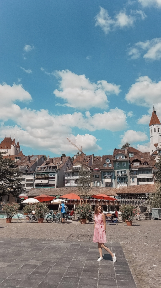 The town of Thun in Switzerland is full of colorful buildings. The white Thun castle rises over the city atop a hill. #Travel #Vacation #Switzerland #Castle #Travelblogs