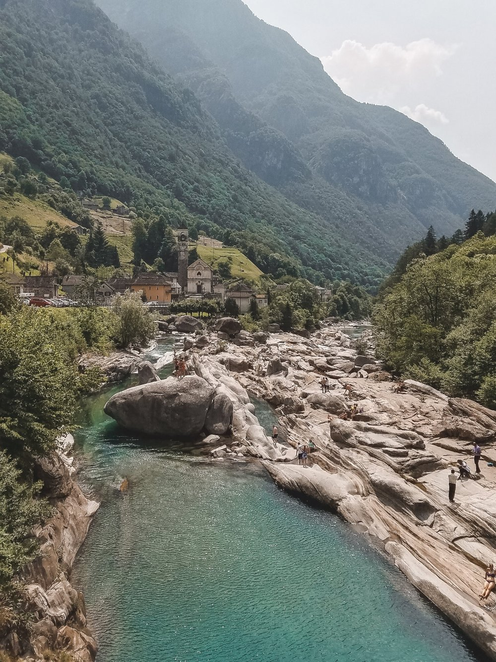 Valle Verzasca Switzerland has crystal clear waters with an emerald hue that flow along smoothed rocks.