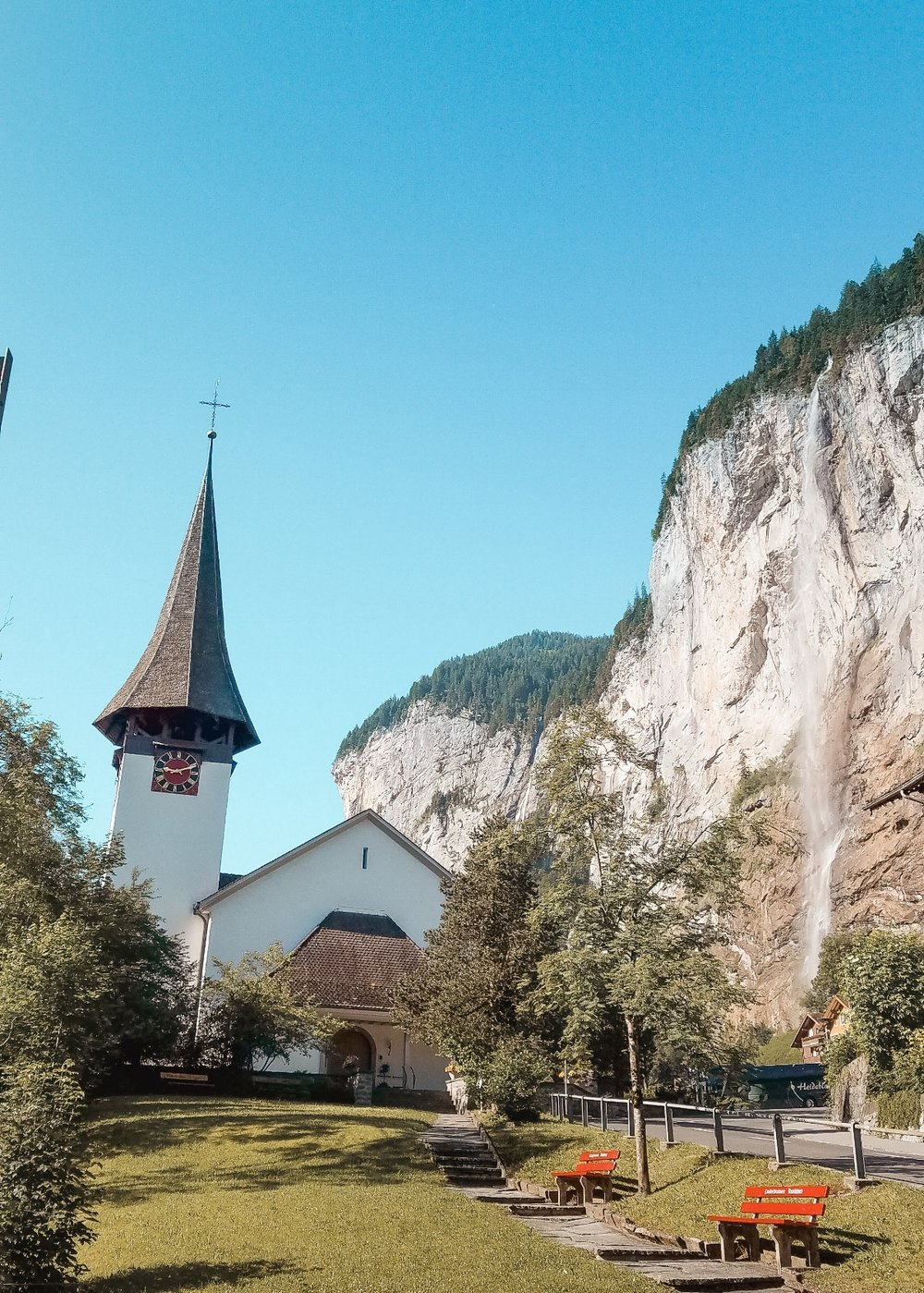The village of Lauterbrunnen in Switzerland is known for its tall waterfall and white church with a steeple.