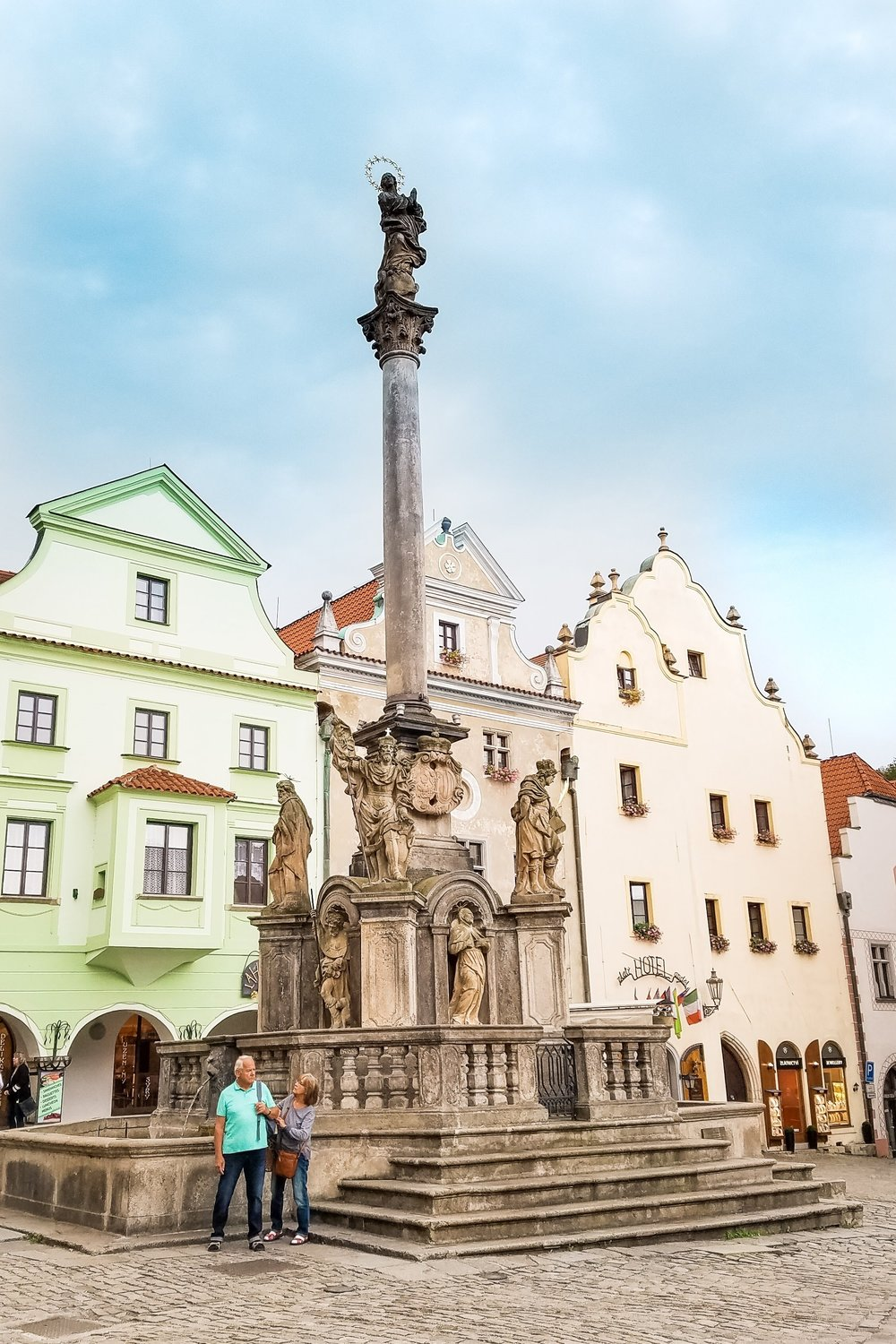 The Plague Column sits in the middle of Cesky Krumlov's town square, surrounded by pastel buildings, hotels and restaurants.