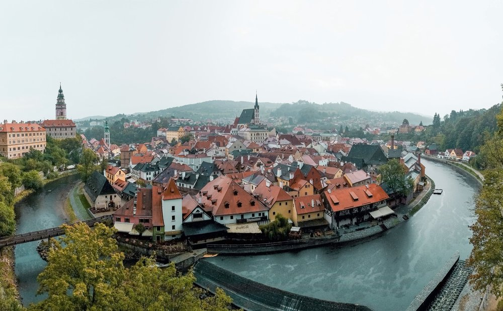 Prague to Cesky Krumlov day trips should include a visit to the hilltop Cesky Krumlov Castle, from where you can see the Vltava River bend around the historic city center pictured here.