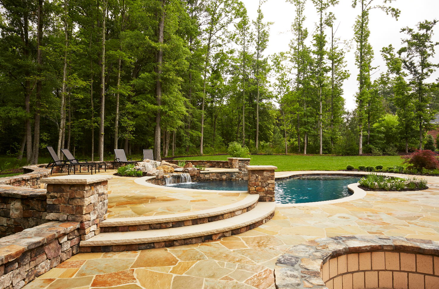 pool with outdoor kitchen cool freeform boulder pool on country estate with contemporary feel builders choice award tudor home outdoor living area with multiple stone waterfall kitchen marcia fryer