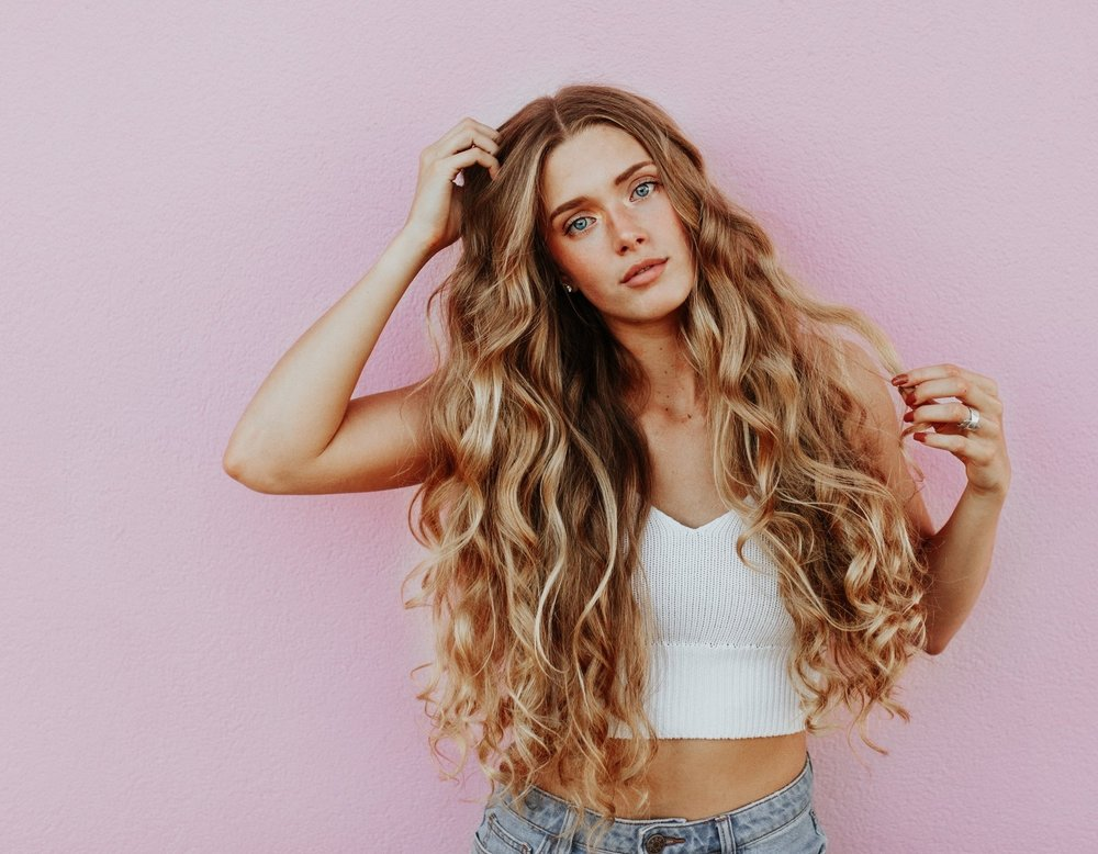 Fashionable woman with long blonde highlights and long hair with curls on pink background