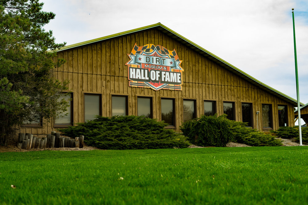 History of DIRT Hall of Fame & Museum   1992: Founded by DIRT promoter Glenn Donnelly. The building was originally intended to house Donnelly's collection of classic cars, but Andy Fusco and Gary Spaid convinced him to include a Hall of Fame for the region's dirt Modified drivers, with historic stock cars on display. Jack Speno was named curator of the Museum. Fusco, Spaid, Gary Rowe and Gary Chadwick drew up a charter, outlining driver eligibility for induction. These four individuals, plus Tom Skibinski, comprised the original selection committee. The inaugural induction ceremonies were held on April 12, 1992, with 12 drivers and one pioneer driver being selected. A set of hero cards and posters were sold, honoring that first class. The ceremonies were followed by a Hall of Fame race at Weedsport Speedway. 1993:The first non-driver racing award was added. Named after Area Auto Racing News founder Leonard J. Sammons Jr., the award was established to recognize outstanding contributions to the sport. Induction criteria was amended to include a provision for active drivers age 55 or older. 1994:The annual number of driver inductees was capped at three maximum, plus a possible pioneer from a past- gone era. The Hall of Fame inductions were moved to the Sunday afternoon of Memorial Dayweekend. 1995: A second award category, honoring car owners, was added. The Hall of Fame and Classic Car Museum was incorporated. 1998:The first annual award for mechanics/engineering was presented. 2002: Gater Racing News announced the addition of an annual Outstanding Woman in Racing Award. 2004: Donnelly sold his racing empire, including the Hall of Fame building, to Boundless Motor Sports Racing. Changes on the selection committee included the departure of Gary Chadwick and the addition of Brian Spaid and Walt Wimer, representing Western PA tracks. 2011:The Hall of Fame race was moved from Weedsport (Cayuga County Fairgrounds) to Rolling Wheels Raceway. 2012:The Cayuga County Fairgrounds facility was closed. Induction ceremonies took place at the Museum as planned, with the Hall of Fame race at Rolling Wheels. 2013: Hall of Fame inductions were moved to June 4, the first evening ceremony. The race took place the next day at Rolling Wheels. Al Heinke purchased the Cayuga County Fairgrounds property from World Racing Group (formerly Boundless), returning the track's name back to Weedsport Speedway. Extensive renovations were begun on the race track, as well as the Hall of Fame and Museum building and the grounds. 2014:The Hall of Fame race was reinstated at Weedsport Speedway in early August as part of the Super DIRTcar Series. Induction ceremonies took place in the Museum theevening prior. 2015: After serving 24 years as chairman of the Hall of Fame selection committee, Gary Spaid stepped down. Buffy Swanson, who was added to the committee in 2012, was announced as the new chair. Upon Andy Fusco's untimely death, the Award for Media Excellence was established in his memory.
