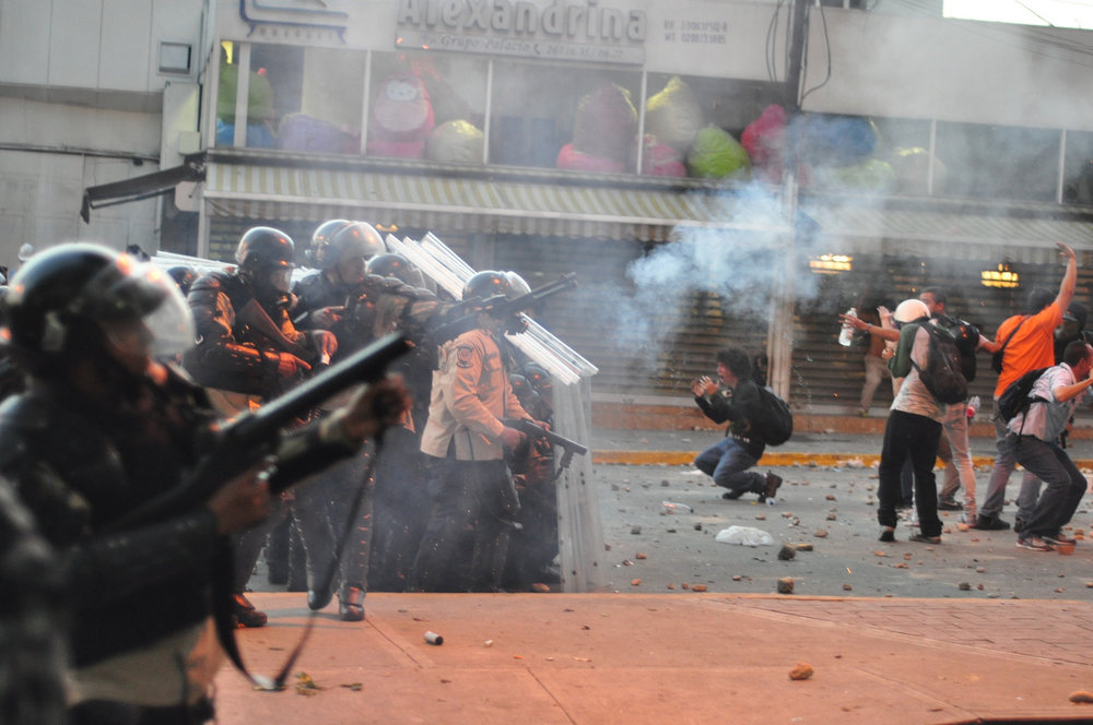 Demonstrators and military personnel clashing in Caracas last year ( source )