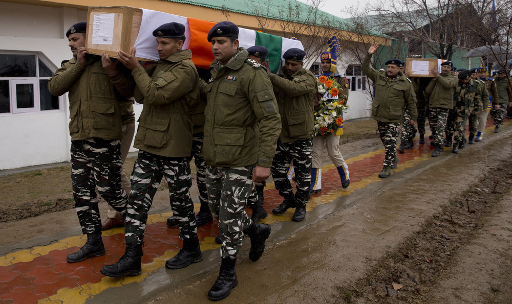 Indian paramilitaries carry the coffins of their fellow soldiers killed in gunfire in Indian-controlled Kashmir ( Image )