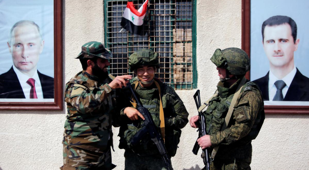 Syrian and Russian soldiers at a checkpoint in Damascus's Wafideen camp in March of last year ( Image )