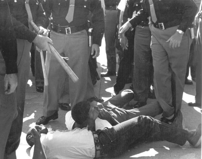 While FBI agents stood by, SNCC volunteers were beaten and arrested by sheriff's deputies for attempting to bring water to people (many elderly) waiting in the hot sun for hours to register to vote in Selma, 1963. Image: © John Kouns.