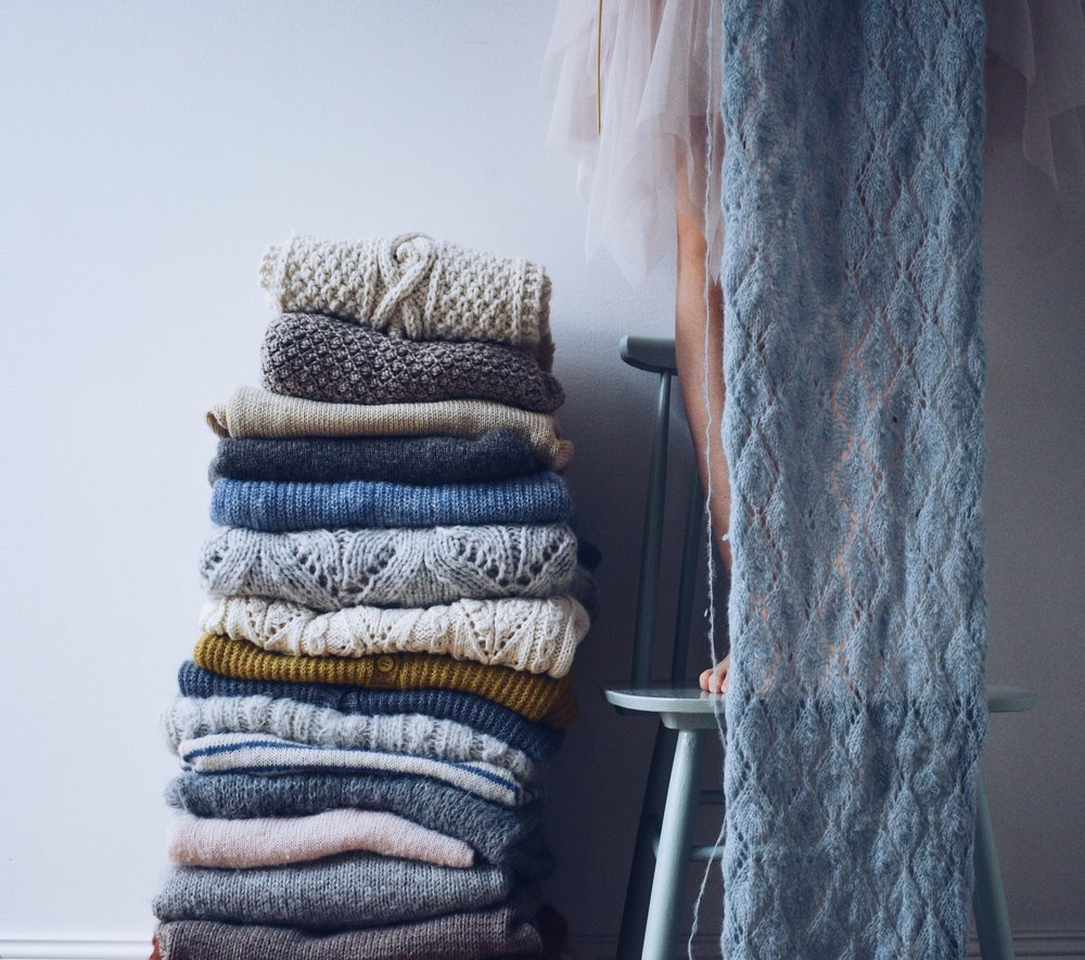A pile of knitted sweaters in neutral tones