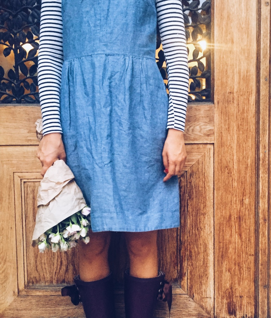 Blue dress and flowers in front of wooden door