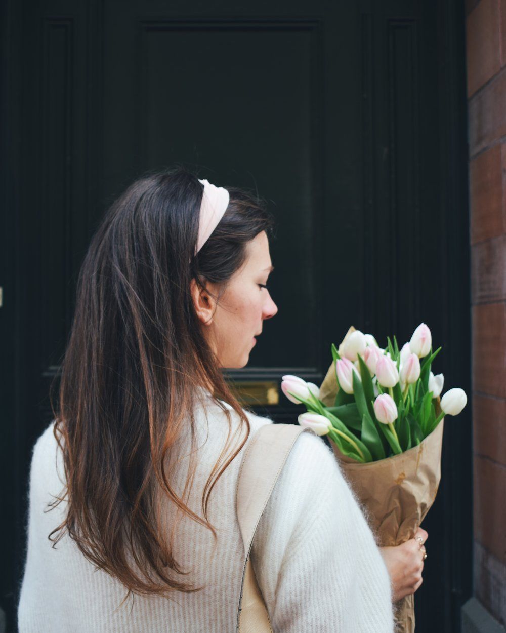 6 comforting thoughts about getting older- standing in front of a green door with tulips and hair band in a white knitted sweater
