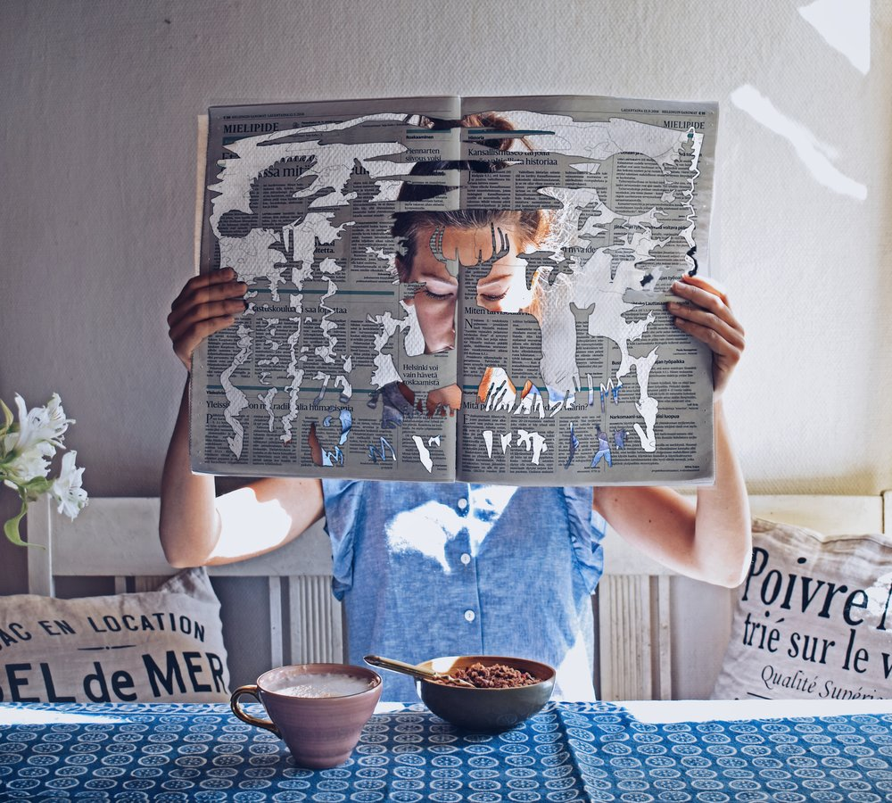 3 photo somposition tips for better storytelling on Instagram- reading the newspaper with a magical faiirytale forest cutout