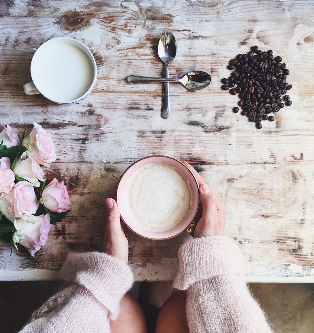 The perfect morning routine- Coffee and milk and flowers on a kitchen table